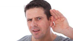 Мужчина держит руку у уха