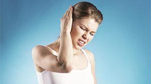 Девушка держится от боли за ухо