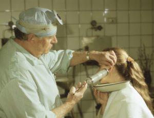 Врач промывает ухо женщине