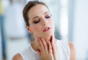 Девушка от боли держится за горло