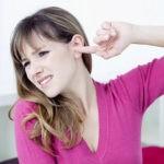 Девушка держит палец в ухе