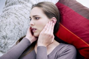 Держится за уши от боли