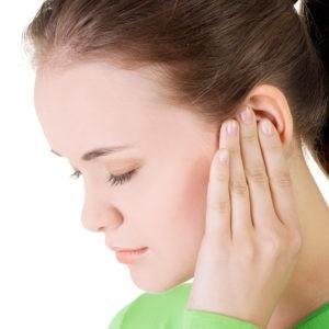 Девушка от боли держится за ухо