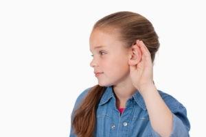 Девочка держит руку возле уха