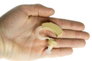 Усилитель слуха лежит на руке