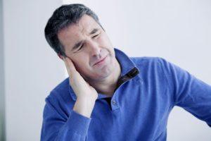Мужчина держится за ухо от боли