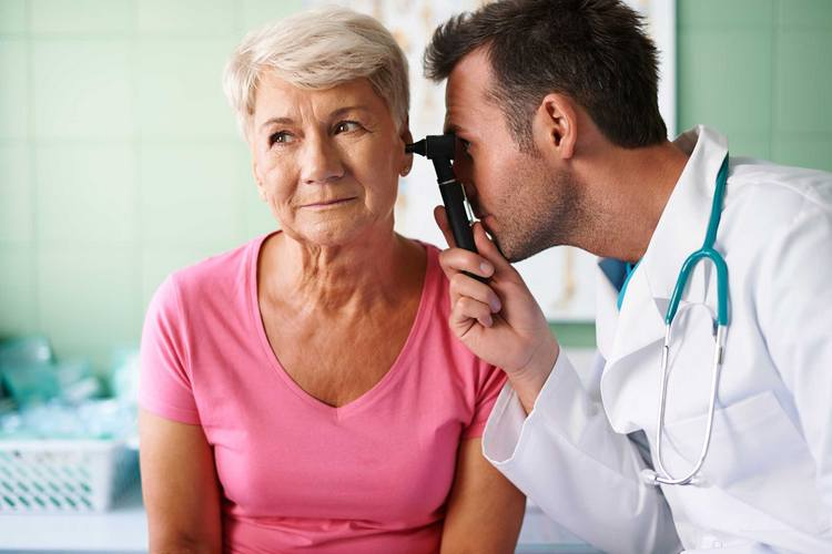 Доктор смотрит ухо пожилой женщине