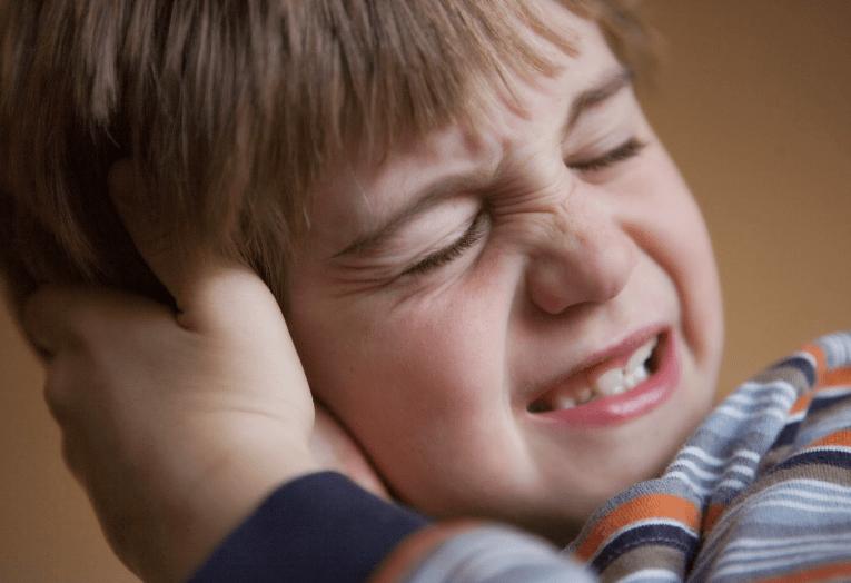 Ребенок держит руки возле уха