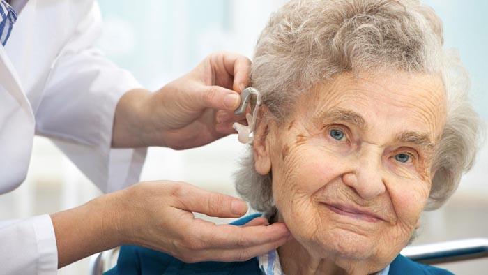 Бабушке вставляют в ухо слуховой аппарат