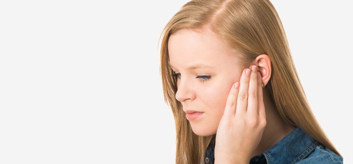 Девушка держится за ухо