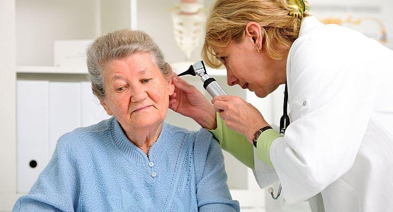 Врач смотрит ухо пожилой женщине