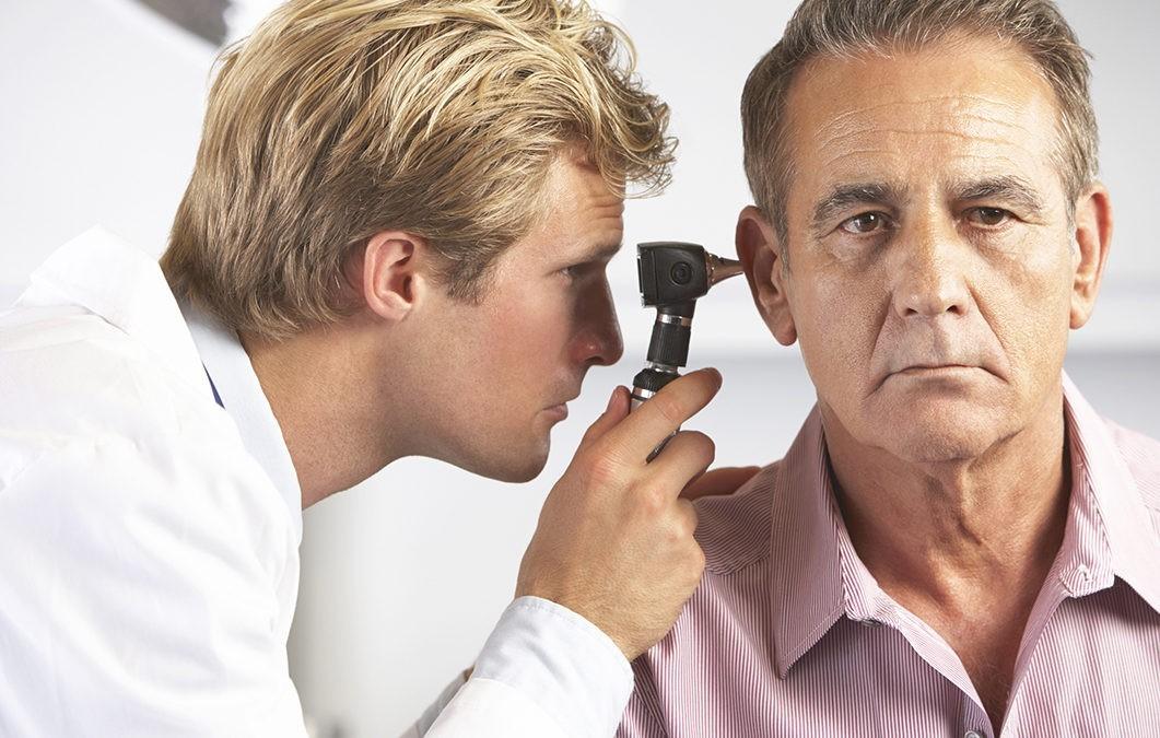 Доктор смотрит ухо мужчине