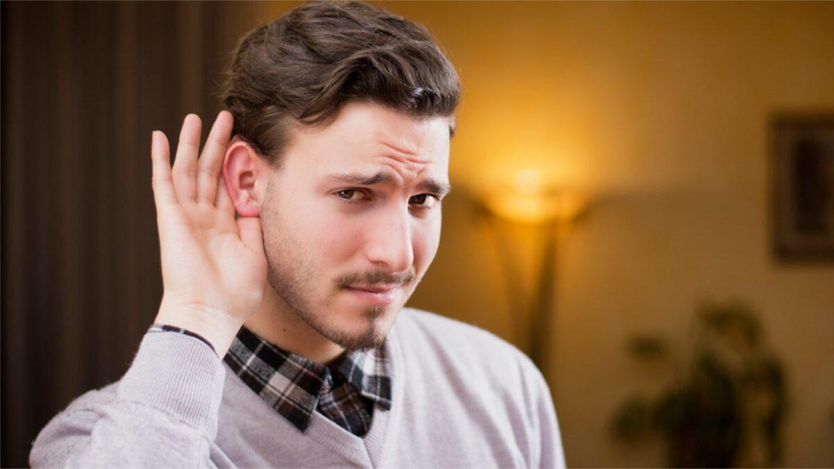 Парень держит руку возле уха