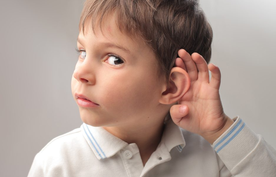 Мальчик держит руку возле уха