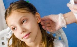 Девочке трогают ухо