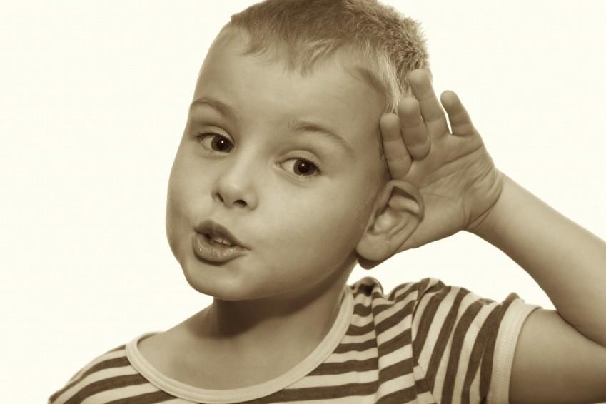 Мальчик приставил руку к уху