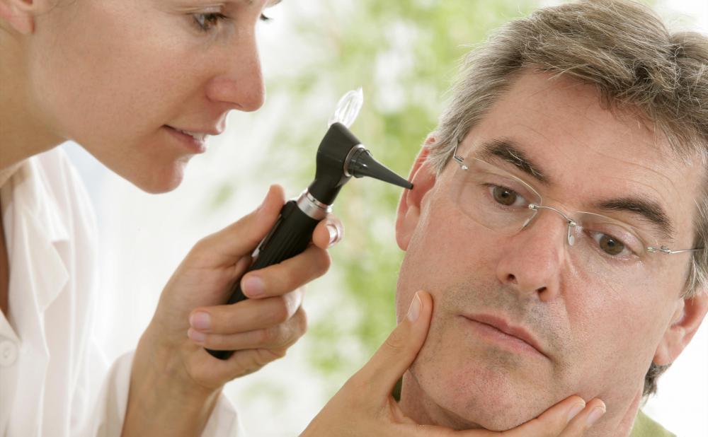 Доктор осматривает ухо мужчины