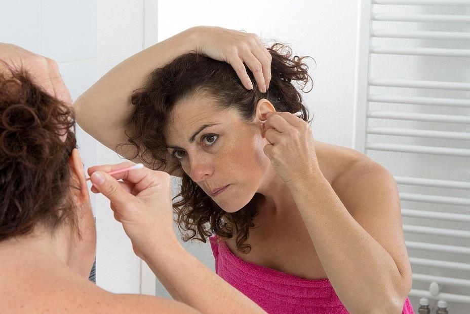 Женщина чистит ухо