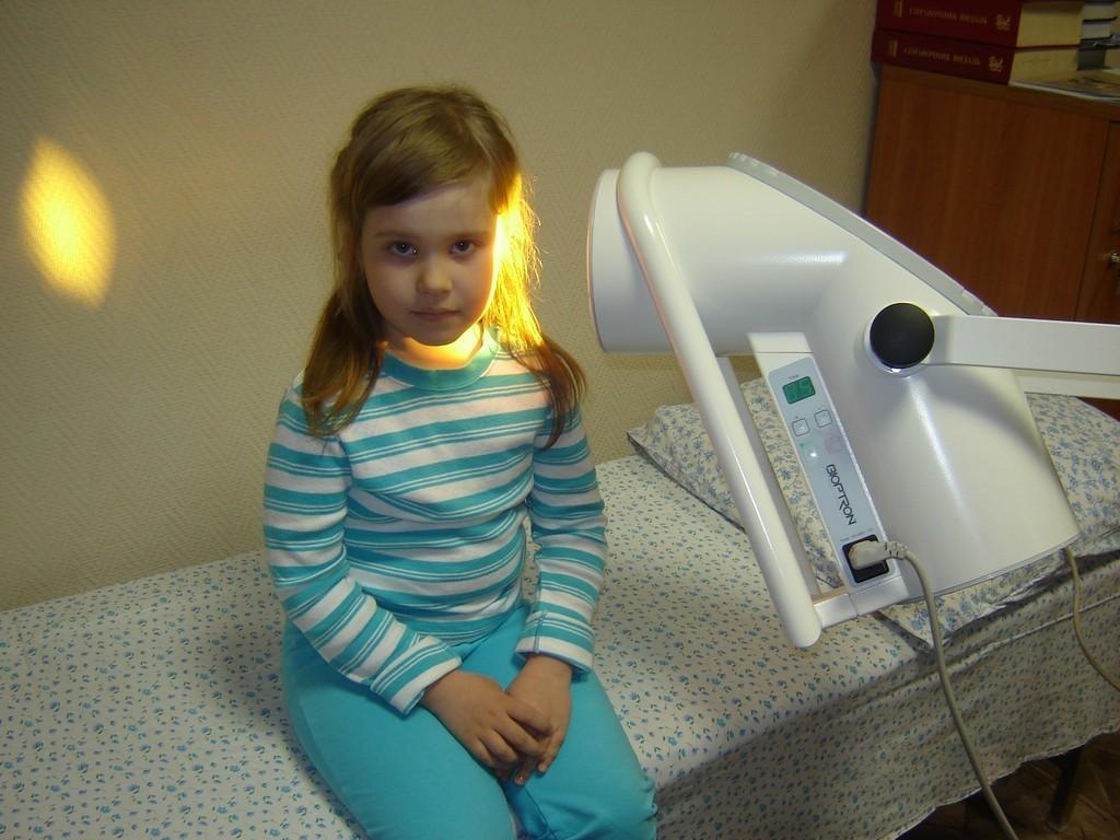 Девочке греют ухо лампой