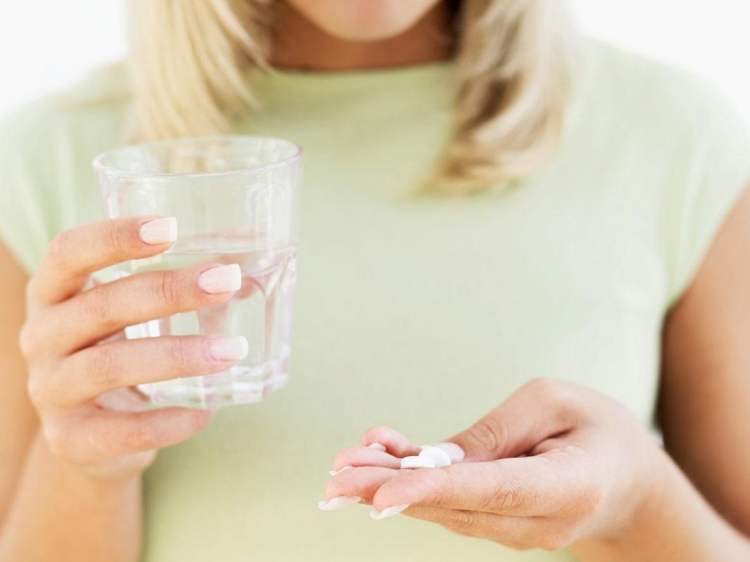 Девушка держит в руках стакан и таблетки