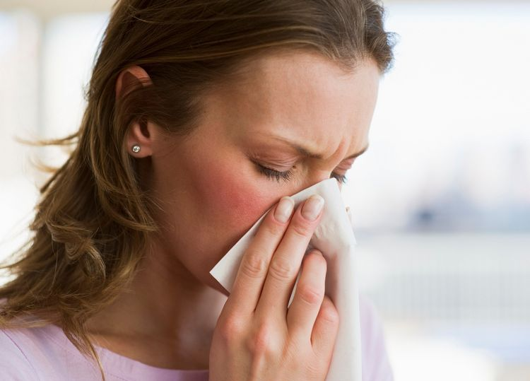 Девушка держит платок у носа