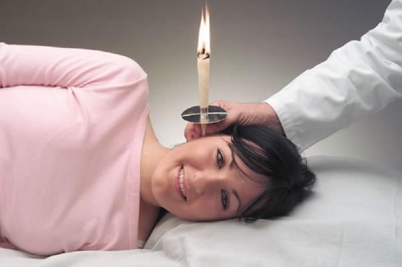 Врач ставит свечу в ухо девушке
