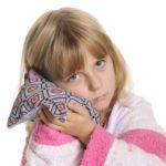 Девочка держит тепло на ухе