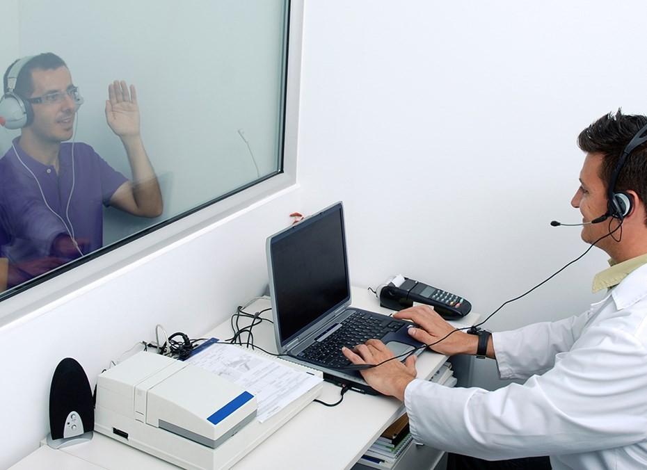 Парень сидит перед доктором за стеклом