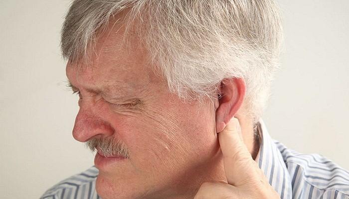 Мужчина нажимает за ухом