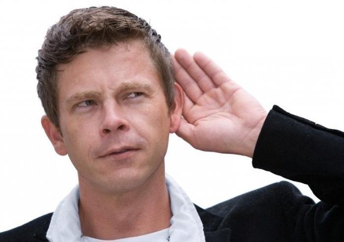 Мужчина держит руку возле уха