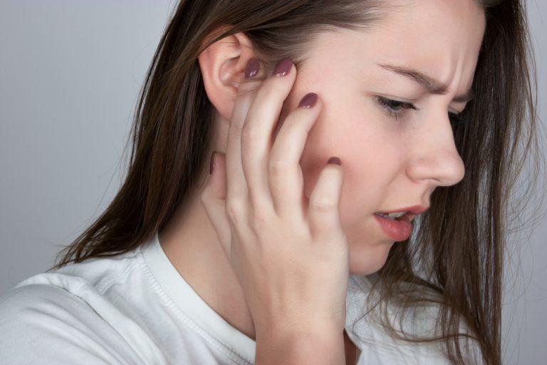 Девушка держит руку возле уха