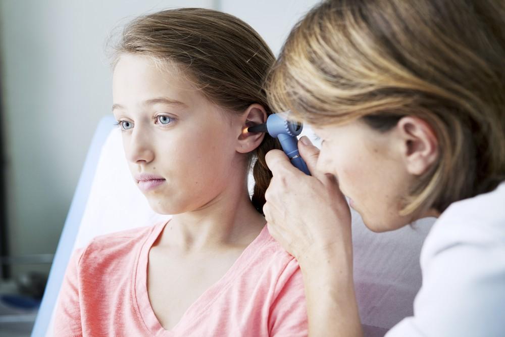 Доктор смотрит ухо девочке